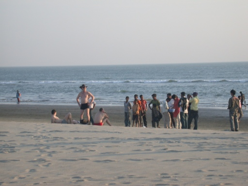 Three Ukrainian men, wearing trunks and briefs, attract attention for immodesty relative to the local norm in Bangladesh.